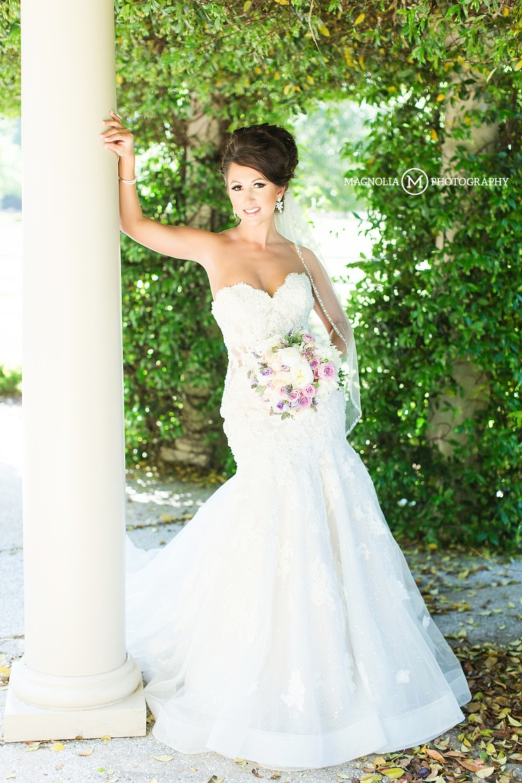 strapless bridal gown leaning on a column